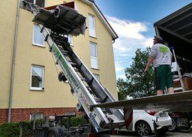 Möbelaufzug vom Fenster zur Ladefläche des Transporters